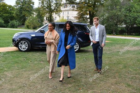 Meghan Duchess of Sussex (C) arrives with her mother, Doria Ragland (L) and Prince Harry to host an event to mark the launch of a cookbook with recipes from a group of women affected by the Grenfell Tower fire at Kensington Palace