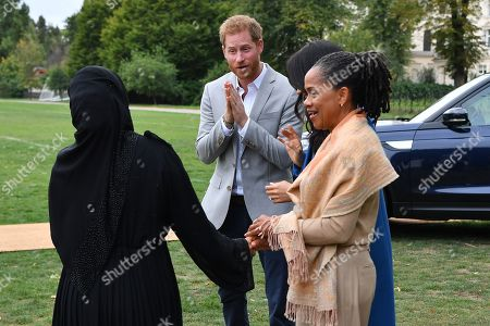 Stock Image of Prince Harry (C), Meghan Duchess of Sussex and her mother, Doria Ragland (R) are greeted by Zahira Ghaswala (L), Hubb community kitchen coordinator to an event to mark the launch of a cookbook with recipes from a group of women affected by the Grenfell Tower fire at Kensington Palace