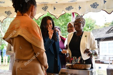 Meghan Duchess of Sussex (C) jokes with her mother Doria Ragland (L) as she helps to prepare food at the launch of a cookbook with recipes from a group of women affected by the Grenfell Tower fire at Kensington Palace