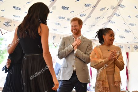 Stock Photo of Meghan Duchess of Sussex (L), her mother, Doria Ragland (R) and Prince Harry take part in the launch of a cookbook with recipes from a group of women affected by the Grenfell Tower fire at Kensington Palace