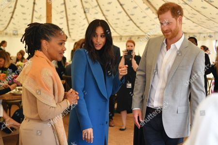 Meghan Duchess of Sussex (C), her mother, Doria Ragland (L) and Prince Harry take part in the launch of a cookbook with recipes from a group of women affected by the Grenfell Tower fire at Kensington Palace