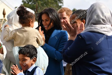 Meghan Duchess of Sussex (C) and Prince Harry gather for a family picture during the launch of a cookbook with recipes from a group of women affected by the Grenfell Tower fire at Kensington Palace