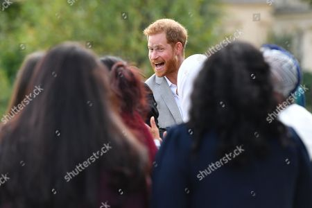 Prince Harry (C) departs after attending the launch of a cookbook with recipes from a group of women affected by the Grenfell Tower fire at Kensington Palace