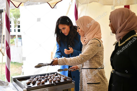 """Stock Photo of Meghan, the Duchess of Sussex, left, cooks with unidentified women behind the cookbook """"Together"""" during a reception at Kensington Palace, in London, . The Duchess was joined by her mother Doria Ragland and husband Prince Harry for the launch of a cookbook aimed at raising money for victims of the Grenfell fire"""