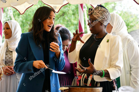 """Meghan, the Duchess of Sussex, left, reacts with one of the women behind the cookbook """"Together"""" during a reception at Kensington Palace, in London, . Markle was joined by her mother Doria Ragland and husband Prince Harry for the launch of a cookbook aimed at raising money for victims of the Grenfell fire"""