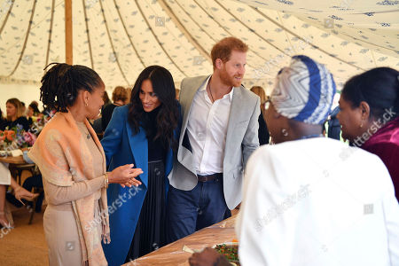 """Meghan Duchess of Sussex, centre, talks to her mother Doria Ragland, with Prince Harry at centre right, as they attend a reception for the cookbook """"Together"""", at Kensington Palace, in London,. The cookbook is being launched with an aim of raising money for victims of the Grenfell fire"""