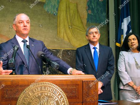 Gov. John Bel Edwards talks about an expected $300 million-plus surplus Louisiana will have from the last budget year, while Commissioner of Administration Jay Dardenne and Revenue Secretary Kimberly Robinson listen to his remarks,, in Baton Rouge, La