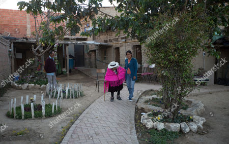 Great-grandniece Rosa Lucas helps her 117-year-old aunt Julia Flores Colque go for a walk outside her home in Sacaba, Bolivia. The Sacaba mayor's office has named Flores Colque a living heritage. The office and a private foundation have improved her home, building the brick path where she walks, and a shower and toilet with a railing so the centenarian can safely make her way to the bathroom at night