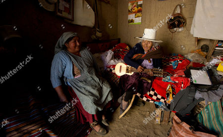 Julia Flores Colque, 117, a native Quechua, right, plays a small five-stringed guitar called charango, while her niece Agustina Berna sits nearby, inside their home in Sacaba, Bolivia