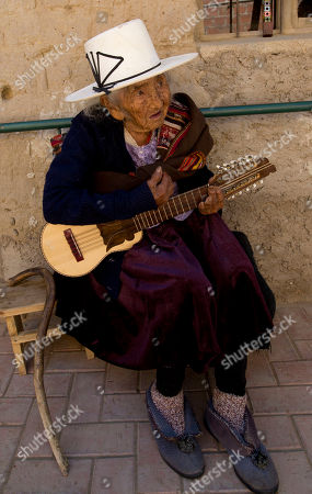 Julia Flores Colque, 117, a native Quechua, sits outside her home with her small five-stringed guitar known as a charango, in Sacaba, Bolivia