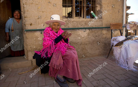 117-year-old Julia Flores Colque sits on her porch, while her niece Agustina Berna stands in the doorway, at their home in Sacaba, Bolivia