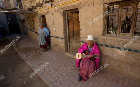 """117-year-old Julia Flores Colque sits on her porch with her """"charango,"""" a small Andean stringed instrument, while her niece Agustina Berna stands nearby, at their home in Sacaba, Bolivia"""
