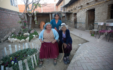 Julia Flores Colque, 117, right, a native Quechua with her niece Agustina Berna, left, and her grandniece Rosa Lucas, pose for a photo in the courtyard of their home in Sacaba, Bolivia. The Sacaba mayor's office has named Flores Colque a living heritage. The previously world's oldest person, a 117-year-old Japanese woman, died earlier this year. Her passing apparently left Flores Colque as the world's oldest living person
