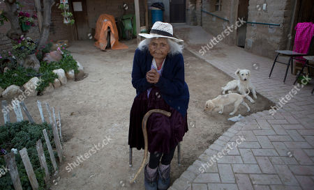 Julia Flores Colque eyes the camera while sitting outside her home in Sacaba, Bolivia, . Her national identity card says Flores Colque was born on Oct. 26, 1900 in a mining camp in the Bolivian mountains. At 117 and just over 10 months, she would be the oldest woman in the Andean nation and perhaps the oldest living person in the world