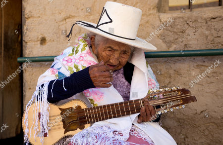 """117-year-old Julia Flores Colque strums a """"charango,"""" a small Andean stringed instrument, at her home in Sacaba, Bolivia. Flores Colque still sings in her indigenous Quechua tongue and strums the five strings of her tiny Andean guitar"""
