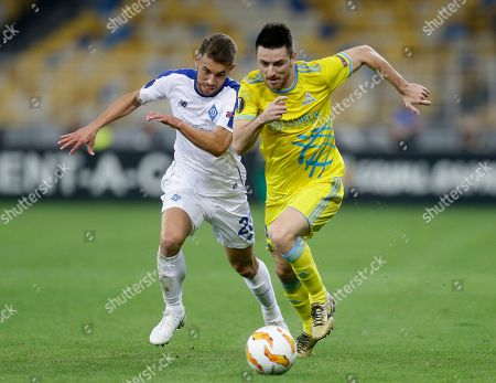 Astana's Antonio Rukavina, right, and Dynamo Kiev's Josip Pivaric challenge for the ball during the Group K Europa League soccer match between Dynamo Kiev and Astana at the Olympiyskiy stadium in Kiev, Ukraine