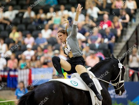 German vaulter, Sarah Kay performs on 1458 Sir Valentin 5 with lunger Dr. Dina Menke in the individual female technical test competition event at the World Equestrian Games, in Tryon, N.C
