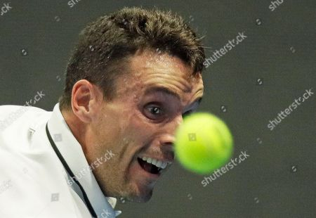 Roberto Bautista of Spain returns the ball to Mikhail Youzhny of Russia during the St. Petersburg Open ATP tennis tournament match in St. Petersburg, Russia