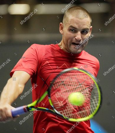 Stock Picture of Mikhail Youzhny of Russia returns the ball to Roberto Bautista of Spain during the St. Petersburg Open ATP tennis tournament match in St. Petersburg, Russia