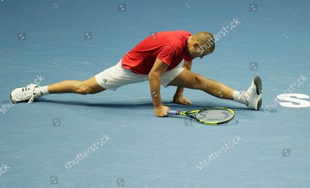 Stock Photo of Mikhail Youzhny of Russia falls down during the St. Petersburg Open ATP tennis tournament match against Roberto Bautista of Spain in St. Petersburg, Russia