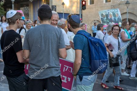 An Israeli man who marches with women, both Arabs and Jews, in a Peace march holds a political discussion with three American Jewish tourists watching the march as it passes in Jerusalem, 20 September 2018. Some two thousand women held the march under the banner 'Women Wage Peace', an initiative that started after the 2014 Gaza war with the goal of pressuring the Israeli government to reach an acceptable bilateral agreement for the Palestinian-Israeli conflict with a target date of 2018. Behind (R) is the Camp David Peace accords handshake between American President Jimmy Carter, Israeli prime Minister Menachem Begin and Egyptian President Anwar Sadat on the White House  in Washington on 17 September 1978, following twelve days of secret negotiations at Camp David.