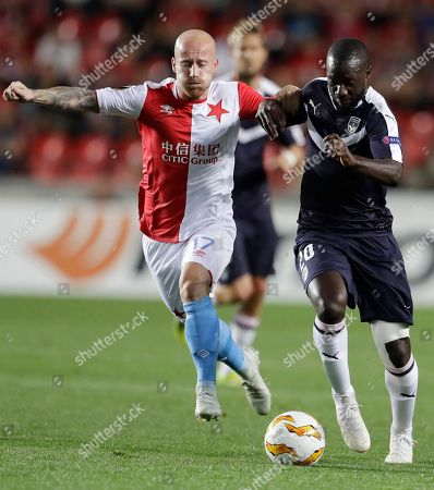 Slavia Prague's Miroslav Stoch, left, challenges Bordeaux's Youssouf Sabaly, right during the Europa League group C soccer match between Slavia Prague and FC Girondins de Bordeaux at the Eden stadium in Prague, Czech Republic