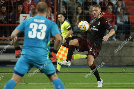 Milan's Ignazio Abate, right, controls the ball as Dudelange's goalkeeper Joe Frising watches during a Group F Europa League soccer match between F91 Dudelange and AC Milan at the Josey Barthel stadium in Dudelange, Luxembourg