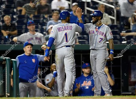 New York Mets' Amed Rosario (1) celebrates with Jose Reyes (7) after Rosario scored on a sacrifice fly by Jose Lobaton during the 12th inning of a baseball game against the Washington Nationals, in Washington. The Mets won 5-4 in 12 innings