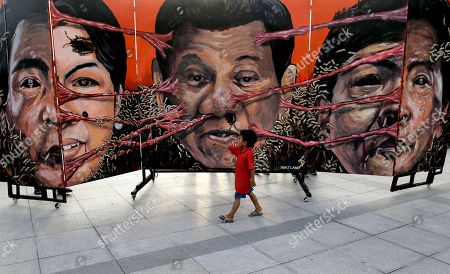 """A boy looks at caricatures of, from left, House Speaker Gloria Macapagal Arroyo, Philippine President Rodrigo Duterte, and former Senator Ferdinand """"Bongbong"""" Marcos Jr. during a rally to call for an end to the killings in the so-called war on drugs of Duterte as well as his alleged """"tyrannical rule"""" of the country, in Manila, Philippines. Protesters are marking the anniversary of the 1972 martial law declaration by the late Philippine dictator Ferdinand Marcos with an outcry against what they say is the current president's authoritarian tendencies and his brutal crackdown on illegal drugs"""