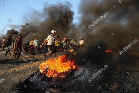Palestinian protesters gather during clashes with Israeli troops in tents protest where Palestinians demand the right to return to their homeland at the Israel-Gaza border, in Khan Younis in the southern of Gaza Strip