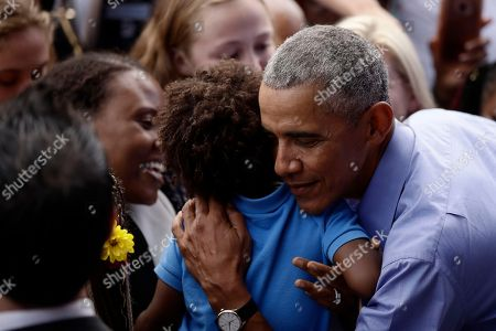 Former President Barack Obama embraces a child as he campaigns in support of Pennsylvania candidates in Philadelphia