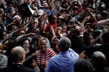 Former President Barack Obama meets with members of the audience as he campaigns in support of Pennsylvania candidates in Philadelphia