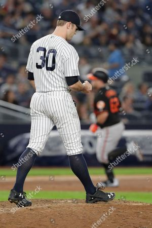 New York Yankees relief pitcher David Robertson (30) reacts as Baltimore Orioles' DJ Stewart runs the bases after hitting a two-run home run during the eighth inning of a baseball game, in New York