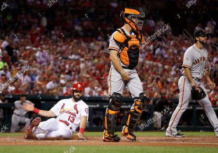 St. Louis Cardinals' Matt Carpenter (13) scores past San Francisco Giants starting pitcher Madison Bumgarner, right, and catcher Nick Hundley during the first inning of a baseball game, in St. Louis