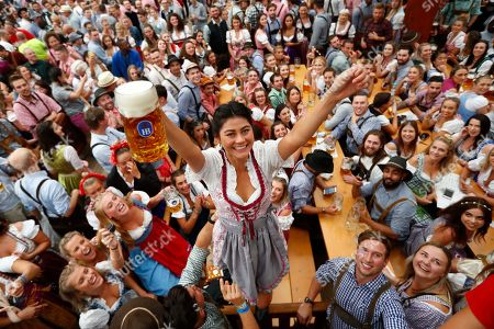 A young woman celebrates the opening of the 185th 'Oktoberfest' beer festival in Munich, Germany, . The world's largest beer festival will be held from Sept. 22 until Oct. 7, 2018
