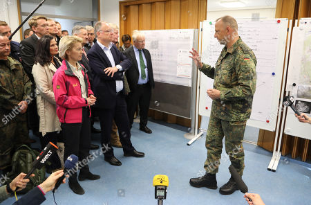The German Minister of Defence, Ursula von der Leyen (C-L), and the State Governor of Lower Saxony, Stephan Weil (C-R) listen to the military leader of the firefighting deployment, Col. Thomas Groeters (R) at the military test site at the Wehrtechnische Dienststelle 91 (WTD 91) of the German Armed Forces (Bundeswehr) near Meppen, northern Germany, 22 September 2018. Hundreds of fire fighters and rescue workers struggle against a  massive moor fire which has extended to several square kilometers since a missile test went wrong more than two weeks ago. The Landkreis Emsland district has given disaster alert as several villages nearby are threatened by the smoke.