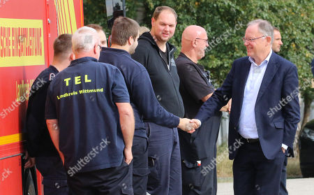 The State Governor of Lower Saxony, Stephan Weil (R), greets rescue workers at the military test site at the Wehrtechnische Dienststelle 91 (WTD 91) of the German Armed Forces (Bundeswehr) near Meppen, northern Germany, 22 September 2018. Hundreds of fire fighters and rescue workers struggle against a  massive moor fire which has extended to several square kilometers since a missile test went wrong more than two weeks ago. The Landkreis Emsland district has given disaster alert as several villages nearby are threatened by the smoke.
