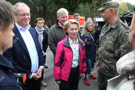 German Minister of Defence, Ursula von der Leyen (C), with  the military leader of the firefighting deployment, Col. Thomas Groeters (R) and the State Governor of Lower Saxony, Stephan Weil (L), at the military test site at the Wehrtechnische Dienststelle 91 (WTD 91) of the German Armed Forces (Bundeswehr) near Meppen, northern Germany, 22 September 2018. Hundreds of fire fighters and rescue workers struggle against a  massive moor fire which has extended to several square kilometers since a missile test went wrong more than two weeks ago. The Landkreis Emsland district has given disaster alert as several villages nearby are threatened by the smoke.