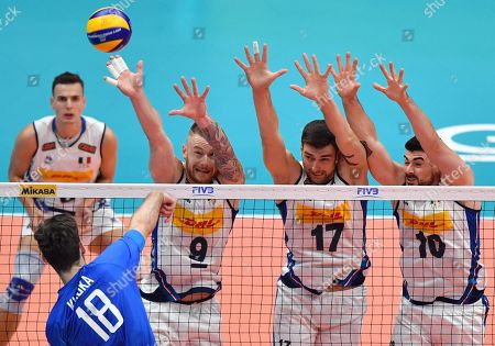 Stock Photo of Russia's Egor Kliuka (L) hits the ball against Italy's Ivan Zaytsev (2L) and temmates Simone Anzani and Filippo Lanza during the FIVB Men's World Championship Pool E second round match Italy vs Russia at the Forum di Assago in Milan, Italy, 22 September 2018.