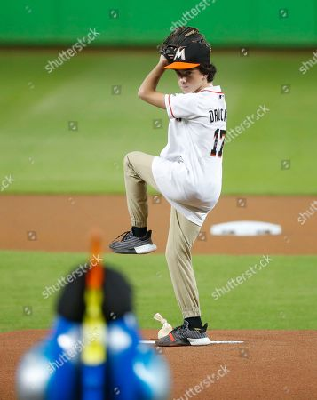 Actor Jason Drucker throws out a ceremonial first pitch before the start of a baseball game between the Miami Marlins and the Cincinnati Reds, in Miami