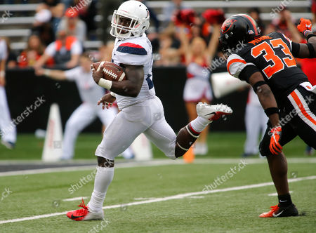 Arizona running back J.J. Taylor looks back at Oregon State's Jalen Moore as he heads to the end zone on a 62 run in the fourth quarter of an NCAA college football game in Corvallis, Ore., . Arizona won 35-14