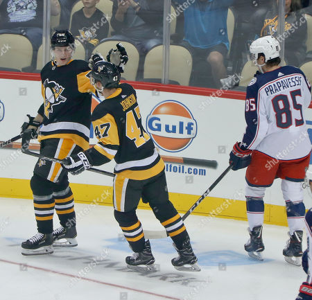 Pittsburgh Penguins' Juuso Riikola, left, celebrates with Adam Johnson (47) after scoring against the Columbus Blue Jackets during the first period of an NHL preseason hockey game, in Pittsburgh