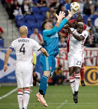 Toronto FC goalkeeper Alex Bono, center left, tries to deflect a pass intended for New York Red Bulls forward Bradley Wright-Phillips, back, as teammate Chris Mavinga (23) helps defend during the second half of a soccer game, in Harrison, N.J. Toronto FC midfielder Michael Bradley (4) looks on during the play
