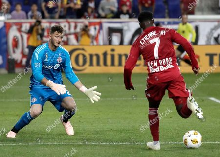 New York Red Bulls midfielder Derrick Etienne (7) drives with the ball before scoring a goal on Toronto FC goalkeeper Alex Bono during the second half of a soccer game, in Harrison, N.J. The Red Bulls won 2-0