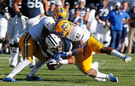 Stock Image of BYU wide receiver Aleva Hifo, center, is tackled by McNeese State's Trent Jackson (9) and Christian Jacobs (42) in the first half during an NCAA college football game, in Provo, Utah