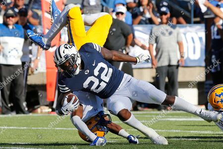 Stock Photo of Trent Jackson, Squally Canada. McNeese State defensive back Trent Jackson, rear, flips as he attempts to tackle BYU running back Squally Canada (22) in the first half during an NCAA college football game, in Provo, Utah
