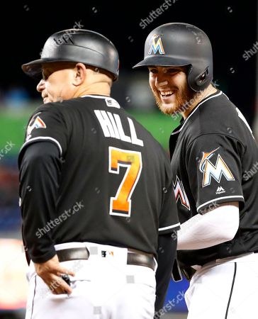 Austin Dean, Perry Hill. Miami Marlins' Austin Dean, right, celebrates with first base coach Perry Hill (7) after getting a base hit scoring Brian Anderson during the fourth inning of a baseball game against the Cincinnati Reds, in Miami