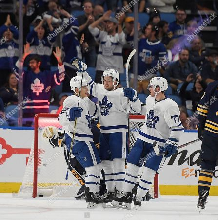 Toronto Maple Leafs left wing Trevor Moore, left, right wing Jeremy Bracco and center Adam Brooks celebrate the Toronto Maple Leafs' second goal during the second period of an NHL preseason hockey game against the Buffalo Sabres in Buffalo, N.Y