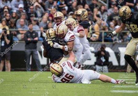 Stock Picture of Boston College defensive lineman Ray Smith (96) and Boston College linebacker Max Richardson (14) make the tackle on Purdue running back D.J. Knox (1) during NCAA football game action between the Boston College Eagles and the Purdue Boilermakers at Ross-Ade Stadium in West Lafayette, Indiana. Purdue defeated Boston College 30-13