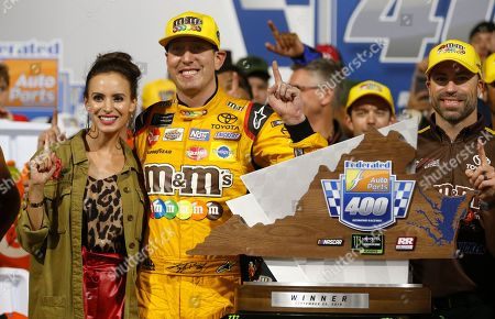 Kyle Busch, Samantha Busch. Kyle Busch (18) poses with the winners trophy and his wife, Samantha, as he celebrates winning the NASCAR Cup Series auto race in victory lane at Richmond Raceway in Richmond, Va